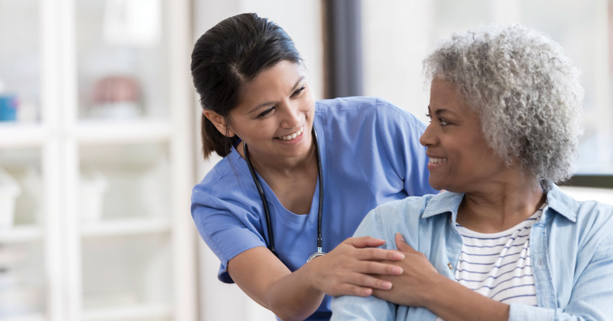 Nurse comforting patient with hand on hand